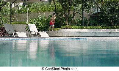 Asian teenager running & jumping into swimming pool in garden slow motion