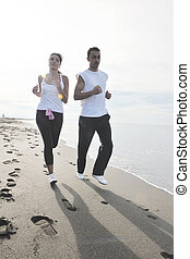couple jogging on the beach - happy young couple running and...