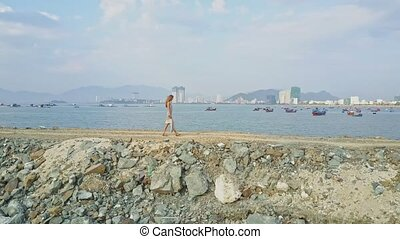Blond Girl Walks on Long Dike in Ocean against Resort City -...