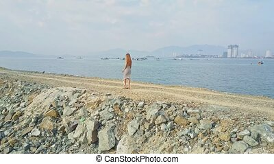 Girl Walks on Ground Ocean Dyke against Boats and City -...