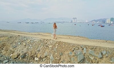 Girl Walks on Dike Takes Photo of Sea Boats against City -...