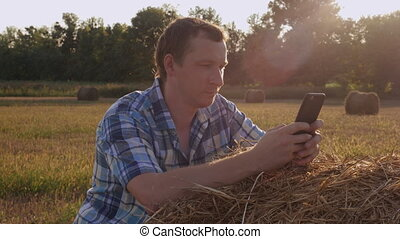 Agronomist have a break use smartphone for chatting. -...