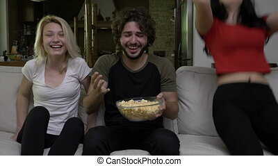 Two young women and a man watch TV together and have a...