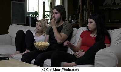 Friends eating popcorn and watching horror movie with very expressive faces