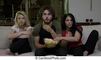Two young women and a guy eating popcorn and watching horror...