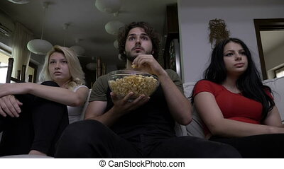 Three friends eating popcorn watch horror movie together and...