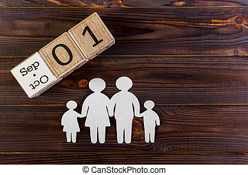 Paper silhouette of family with September 1 on a decorative calendar on wooden background. Life insurance concept