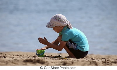 Little boy playing with sand on the beach