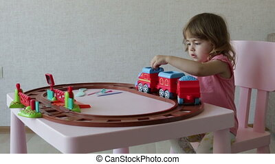 a girl playing with her toy trains on track - happy little...