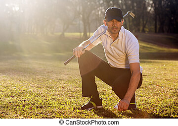 golfer on playing field - The golfer is squatting on the...