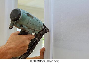 Carpenter brad using nail gun to moldings on doors, framing...