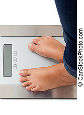 Bathroom scales - Young woman weighing herself - isolated on...