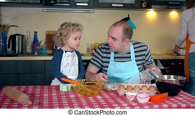 Portrait of happy family making cake together in kitchen