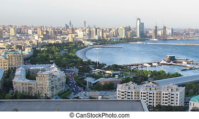 Top View of a Big City by the Sea. Day to Night. Baku,...