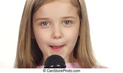 Child girl sings the song into the microphone. White...
