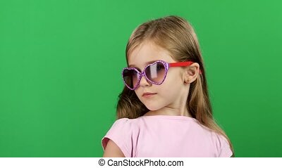Baby posing for video cameras with glasses. Green screen -...