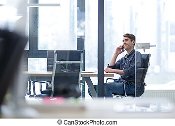 Young casual businessman using smartphone in the startup...