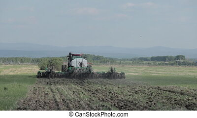 Tractors preparing land for sowing, summer. field