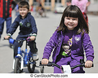 happy childrens group learning to drive bicycle outdoor at...
