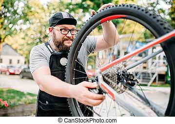 Bicycle repairman works with bike wheel, cycle workshop...