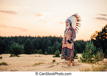 American Indian woman looks in a distance outdoors....