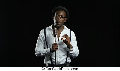 African American in a studio is singing songs into a microphone. Black background
