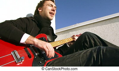 Lone artist - Male musician playing the guitar and sings...