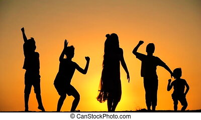 silhouette of five kids jumping against sunset