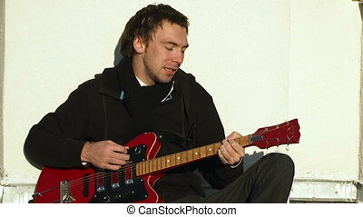 Guitarist plays guitar - A man sits leaning back against a...