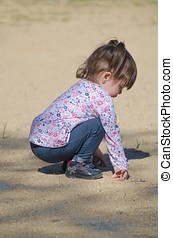Pretty little girl squatting and playing in the ground with...