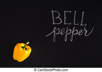 Shinny yellow bell pepper with the inscription over black...