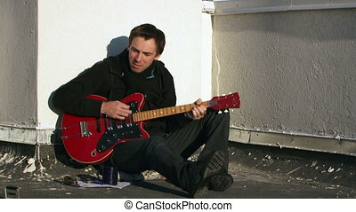 Relaxed musician - A man sits leaning back against a white...