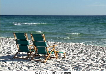 Beach Chairs - Two vacant reclining chairs sit side by side...