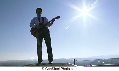 Guitarist silhouette - Well-dressed man playing guitar in...