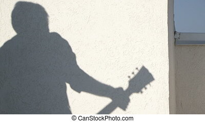 Shadow guitarist - On the wall shadow of a man playing the...