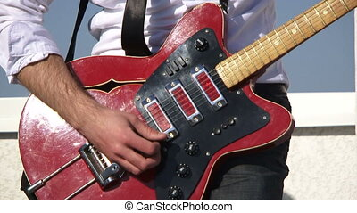 Rock musician emotionally plays guitar Close-up