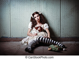 Portrait of strange lonely girl with dolls in abandoned...