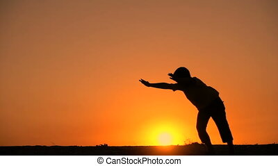 Silhouette of boy standing somersault against sunset, slow...
