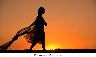 Silhouette of young girl walking against sunset