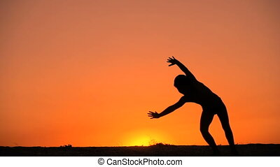 Silhouette of boy making somersault against sunset, slow...