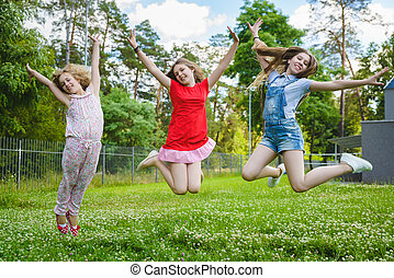 Children jumping on grass in park