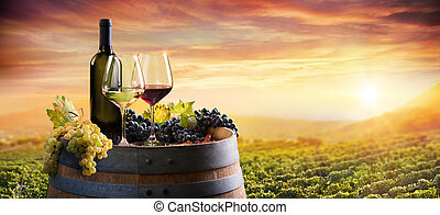 Bottle And WineGlasses On Barrel In Vineyard At Sunset