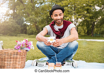 Smiling young african american man having picnic in park