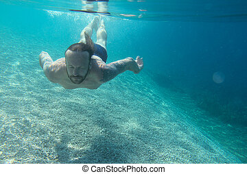 Man swimming underwater in blue transparent sea water