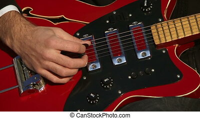 Red guitar - Guitarist actively playing the guitar Close-up...