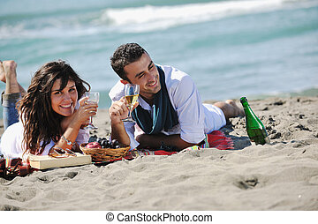 young couple enjoying picnic on the beach - happy young...