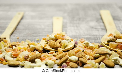 Type of nuts and sweet in wooden spoon on wooden background.