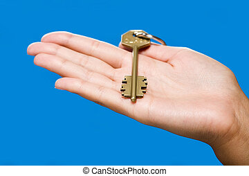 Golden key lying on the hand on the blue background