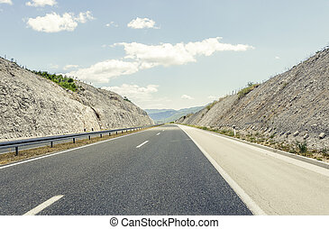 Highway outside the city receding into the highlands. Travel...