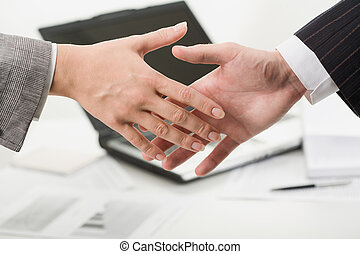 Welcome - Woman and man shaking hands on the background of...